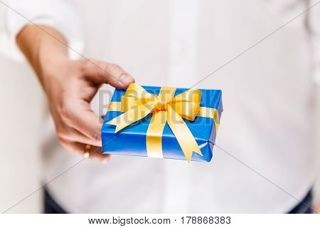 Male hand holding a gift box. Present wrapped with ribbon and bow. Christmas or birthday blue package. Man in white shirt.