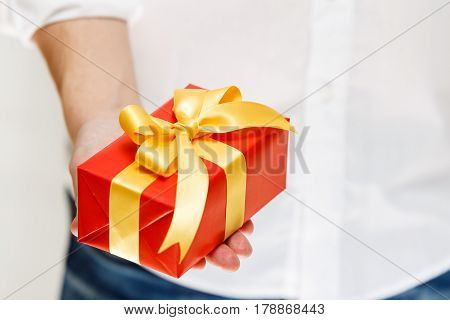 Male hand holding a gift box. Present wrapped with ribbon and bow. Christmas or birthday red package. Man in white shirt.