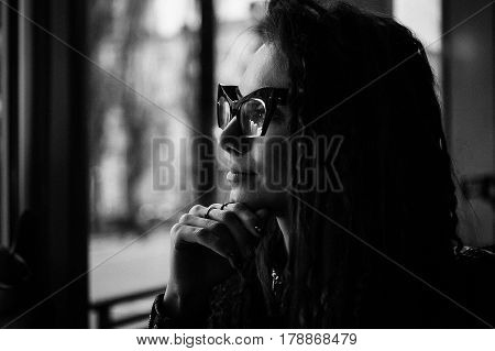 Close-up face portrait of young beautiful woman in Cat's eye glasses in cafe. Romantic concept. Lady looking in the window.