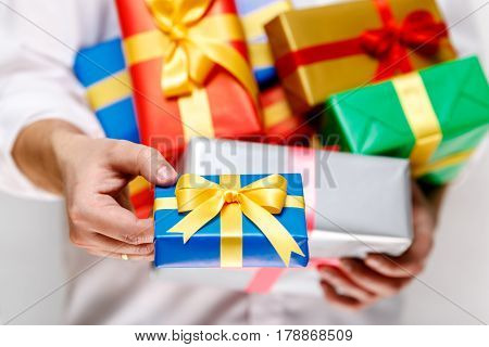Male hands holding a gift boxes. Presents wrapped with ribbon and bow. Christmas or birthday packages. Man in white shirt give box.