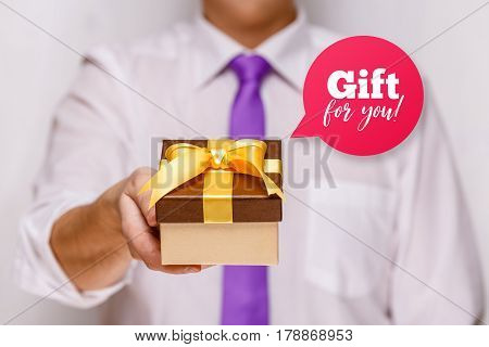 Male hand holding a gift box. Present wrapped with ribbon and bow. Gift for you speech bubble. Man in white shirt and necktie.