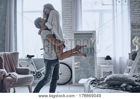 Expressing their love. Handsome man in white T-shirt carrying young attractive woman while spending free time at home