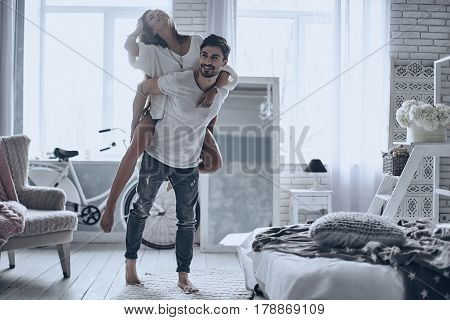 Always happy together. Young couple having fun in bedroom at home while handsome man giving his girlfriend piggy back ride