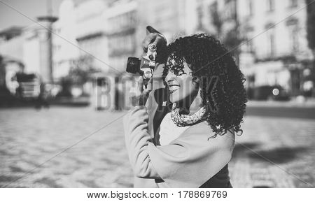 Black and white view of beautiful woman while making shoot on vintage camera greyscale portrait of curly Brazilian lady in coat and sweater using retro camera with copy space for your text message