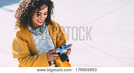 Attractive Brazilian woman with vintage camera adult white smiling curly lady in yellow coat using retro photo camera with copy space for young advertising text message or promotional content