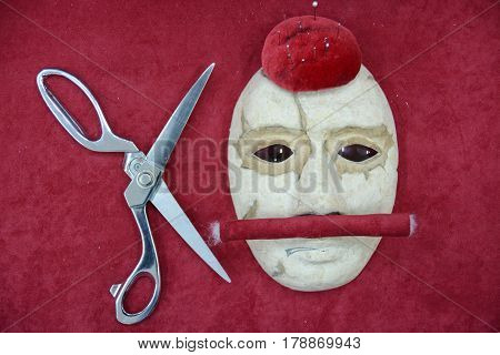 Theatrical mask and tailor's scissors lie on red velvet