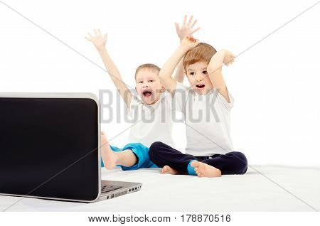 Two joyful children, sitting in front of a laptop screen, isolated on a white background