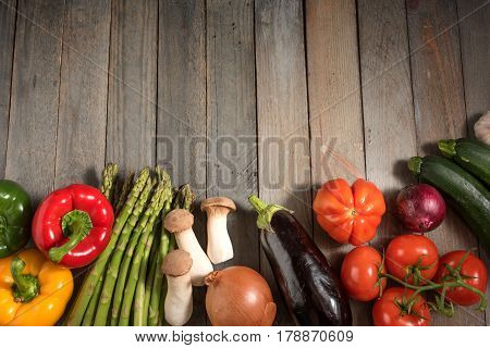 Fresh asparagus and other vegetables on rustic wooden table for a healthy nutritional concept