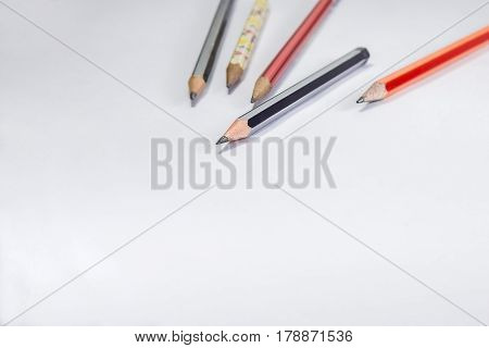 Back to school concept- a Pencilerasor sharpner an cut slice of the pencil on white table with or without spectacles not properly aranged isolated.