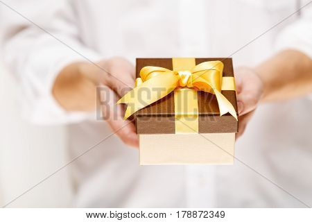 Male hands holding a gift box. Present wrapped with ribbon and bow. Christmas or birthday package. Man in white shirt.