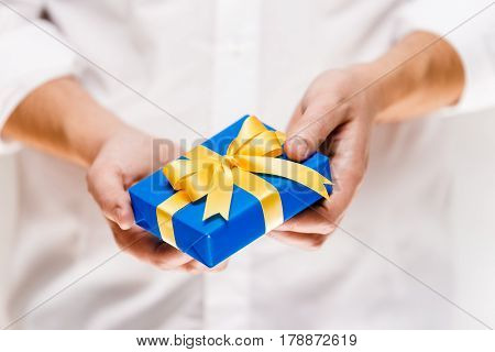 Male hands holding a gift box. Present wrapped with ribbon and bow. Christmas or birthday blue package. Man in white shirt.