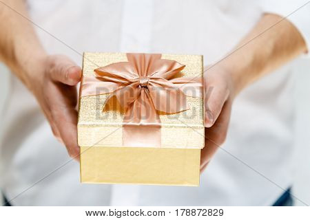 Male hands holding a gift box. Present wrapped with ribbon and bow. Christmas or birthday golden paper package. Man in white shirt.