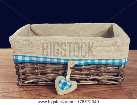 A wooden knitted basket on a wooden table on it burlap and cloth in a box, as well as a heart of burlap