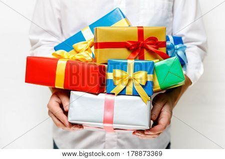 Male hands holding a gift boxes. Presents wrapped with ribbon and bow. Christmas or birthday colored packages. Man in white shirt.