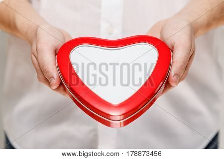 Male hands holding a heart-shaped gift box. Present wrapped with ribbon and bow. Valentines day love package. Man in white shirt.