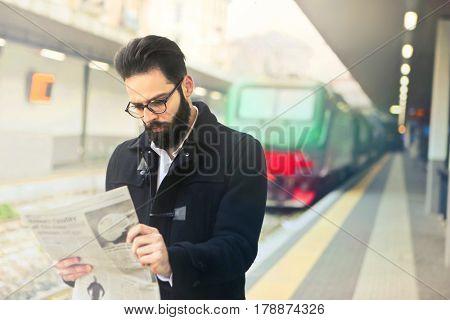 Man waiting on the railway platform reading the newspaper