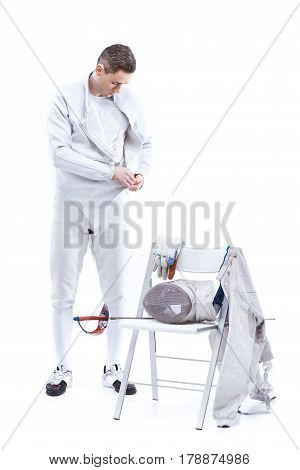 Young Man Professional Fencer Putting On Protective Costume On White