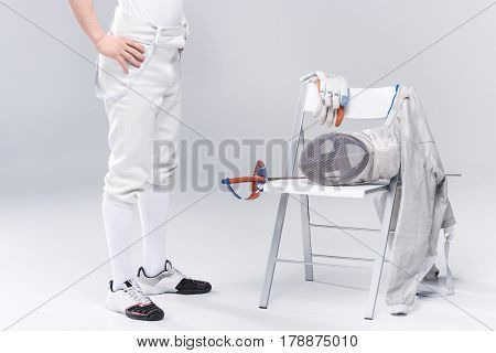 Low Section Of Young Man Professional Fencer Standing Near Chair With Fencing Equipment