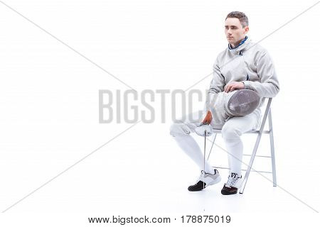 Young Man Professional Fencer Holding Sword And Mask While Sitting On Chair