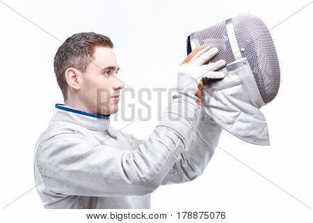 Side View Of Young Man Professional Fencer Wearing Helmet On White