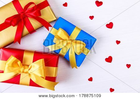 Gift boxes with red satin hearts. Presents wrapped with yellow ribbon. Christmas or birthday packages. On white wooden table.