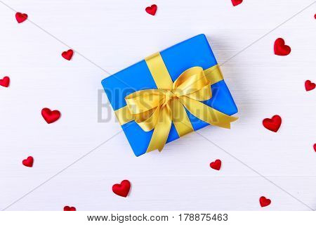 Gift box with red satin hearts. Present wrapped with yellow ribbon. Christmas or birthday blue package. On white wooden table.