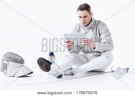 Fencer In Uniform Using Digital Tablet While Resting After Training On White
