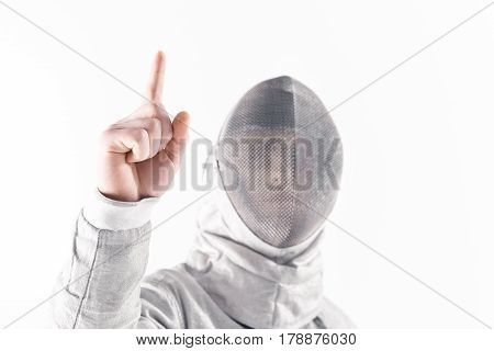 Portrait Of Professional Fencer In Fencing Mask Pointing Up On White