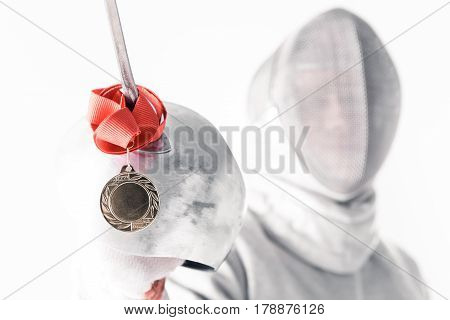 Portrait Of Professional Fencer In Fencing Mask Holding Medal And Rapier On White