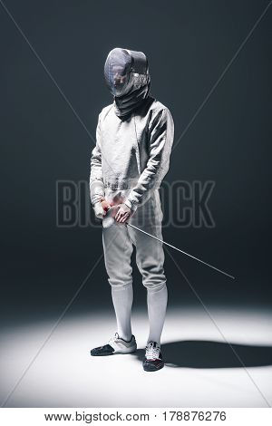 Professional Fencer In Fencing Mask With Rapier Standing On Grey