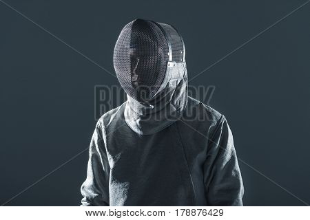 Portrait Of Professional Fencer In Fencing Mask Standing On Grey