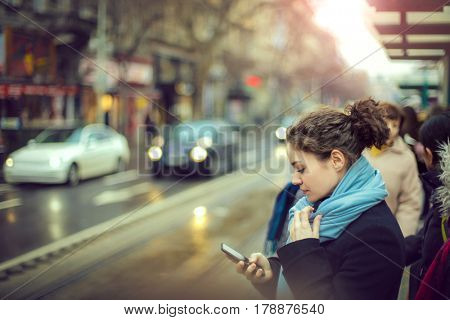 Checking the smartphone while waiting for the bus to come