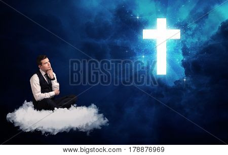 Caucasian businessman sitting on a white fluffy cloud looking and wondering at a big bright glowing cross