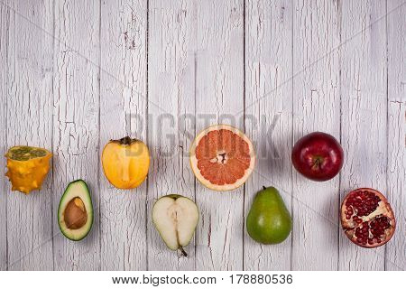 Composition of fruits in a checkerboard pattern placed on a white or grey wooden board
