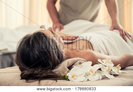 Young woman relaxing on massage bed under the positive therapeutic effect of a crystal placed on her forehead at luxury spa and wellness center