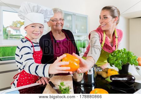 Granny, mum and son talking while cooking in kitchen