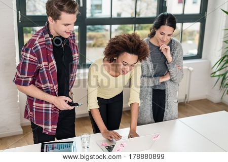 Three young colleagues laughing while standing in front of a laptop in the meeting room of a modern company