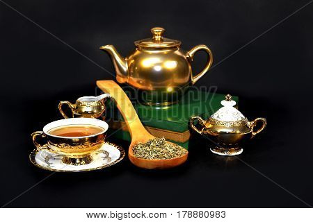Golden tea set with a spoon full of herbs on on the dark background