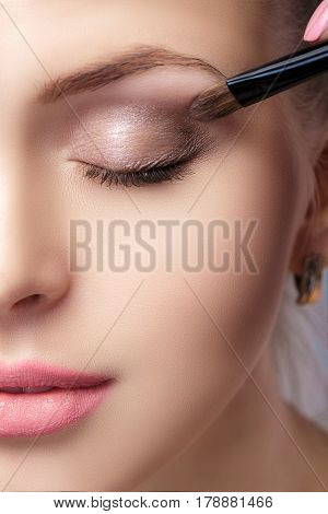 beautiful woman applying brown eye shadow using a brush for makeup. makeup for blue eyes