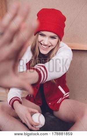 Stylish Hipster Woman In Baseball Jacket With Baseball Ball Giving Highfive