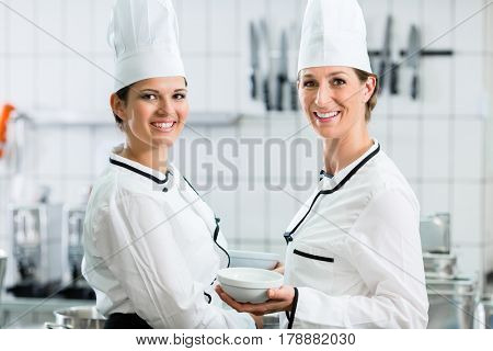 Two female chefs in gastronomic kitchen wearing white cooking uniforms