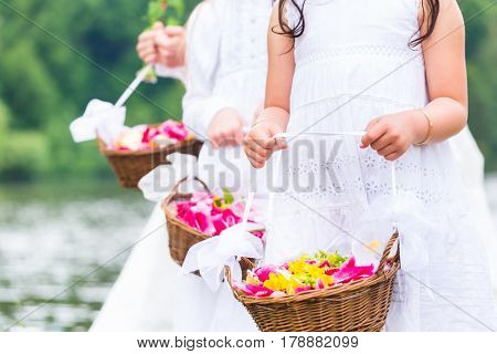 Wedding couple bride and groom with flower children or bridesmaid in white dress