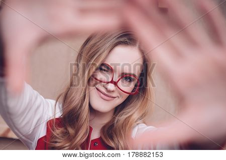Stylish Hipster Woman With Red Eyeglasses Making Focus Framing Gesture And Blinking