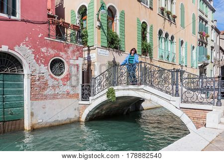 Woman Is Standing On Ponte Giustinian In Venice, Italy