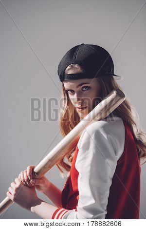 Attractive Young Woman In Cap Holding Baseball Bat And Looking At Camera