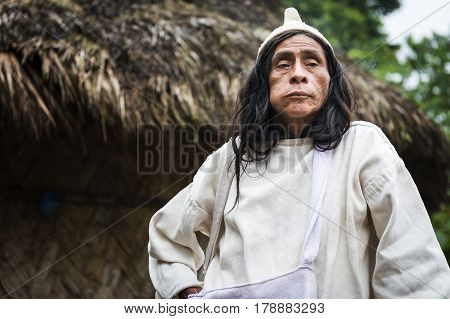 Sierra Nevada de Santa Marta Colombia - March 8 2014: Kogi Mamas (shaman) chewing coca leaves in front of a hut in the forest in the Sierra Nevada de Santa Marta Colombia