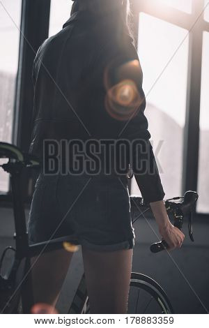 Back View Of Young Stylish Woman Riding Bicycle