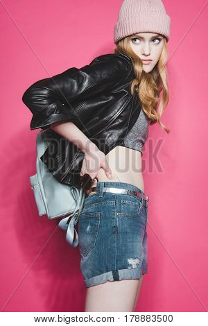 Side View Of Stylish Young Woman In Leather Jacket On Pink