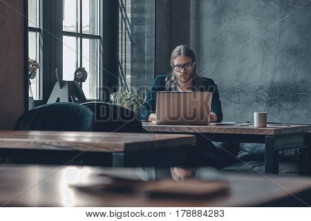 Full concentration at work. Serious young man in smart casual wear working using computer while sitting at the office desk