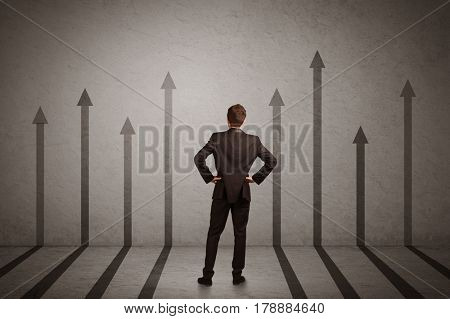 Sales person in doubt looking at arrows pointing up on the wall concept